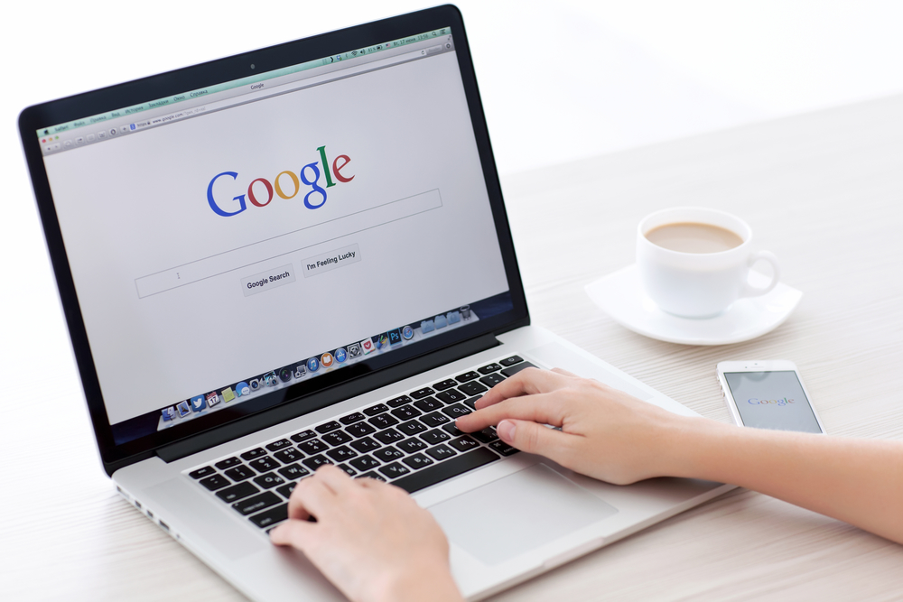 person performing a google search on a laptop